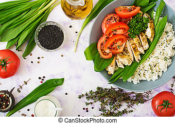 Healthy salad with chicken, tomatoes, wild garlic and rice. ...