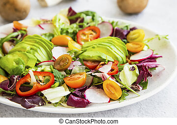 Healthy salad with fresh vegetables, avocado, tomatoes, pepper, radishes, green arugula, onion, spinach and lettuce with olive oil