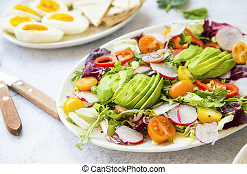 Healthy salad with fresh vegetables, avocado, tomatoes, pepper, radishes, green arugula, onion, spinach and lettuce with olive oil, healthy vegan eating closeup
