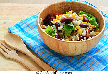 Healthy salad with fresh vegetables on wood background