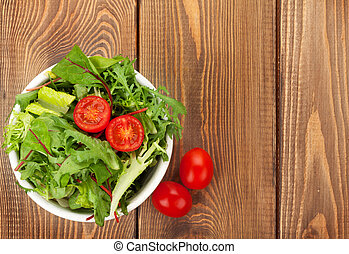 Healthy salad with tomatoes on wooden table
