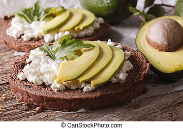 Healthy sandwiches with avocado, cream cheese and arugula close-up
