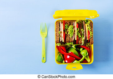 Healthy school lunch box with beef sandwich and fresh vegetables on blue background. Top view. Flat lay