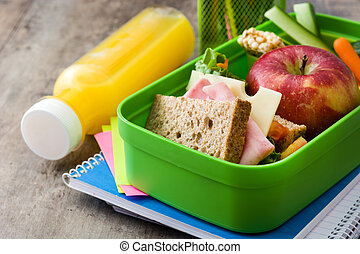 Healthy school lunch: Sandwich, vegetables ,fruit and juice on wooden table.
