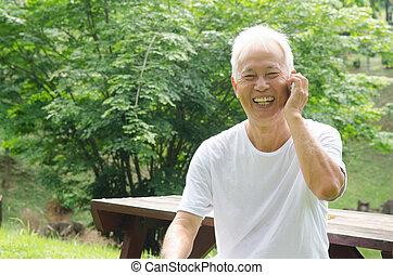 Healthy senior Asian man on the phone outdoor green park