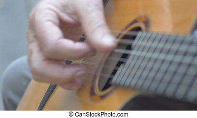 Healthy senior man hands strumming and playing acoustic guitar