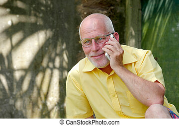 Healthy senior man on the phone outdoor garden