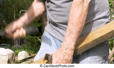 Healthy senior man removing a nail from a piece of wood...
