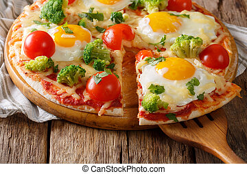 Healthy sliced pizza with eggs, broccoli, tomatoes and parsley close-up. horizontal