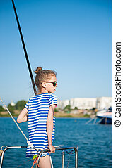 healthy small caucasian girl in sunglasses and striped sailor shirt standing on board of boat in sea port during summer vacation travel