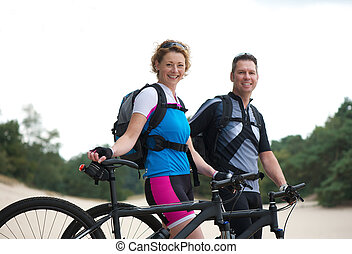 Healthy smiling couple standing with their bikes outdoors