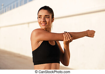 Healthy smiling lady making exercises and stretching hands while training