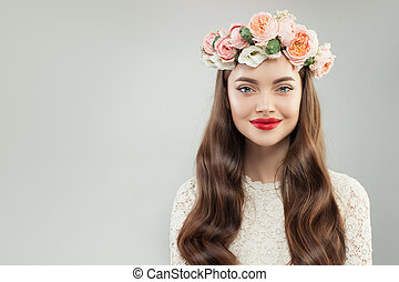 Healthy Smiling Model Woman with Clear Skin, Long Curly Hair, Makeup and Flowers on White Background