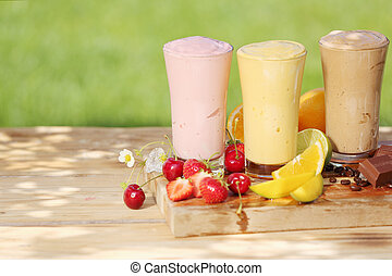 Three healthy smoothie milkshake drinks in tall glasses, natural tones