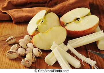 A healthy snack with pistachio nuts, apples and string cheese