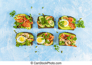 Healthy snack or appetizer toast with salmon, avocado, shrimps, eggs, cucumber, lambs lettuce or corn salad and parsley. Top view, light blue table surface