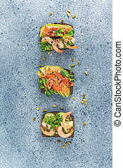 Healthy snack or appetizer toast with salmon, avocado, shrimps, eggs, cucumber, lambs lettuce or corn salad and parsley. Light grey table surface