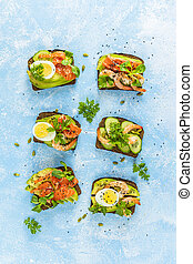 Healthy snack or appetizer toast with salmon, avocado, shrimps, eggs, cucumber, lambs lettuce or corn salad and parsley. Top view
