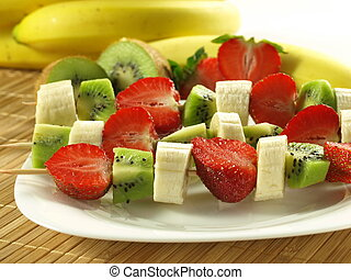 Plate of healhty fruit shashliks: banana, strawberry and kiwi