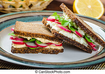 Healthy snack - wholemeal bread with egg-cream spread and fresh vegetable arugula and radishes