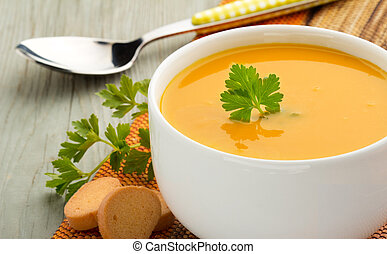 healthy soup - bowl of soup, parsley and croutons on wooden...