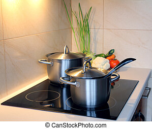 healthy soup with vegetables in the kitchen , pot on induction hob