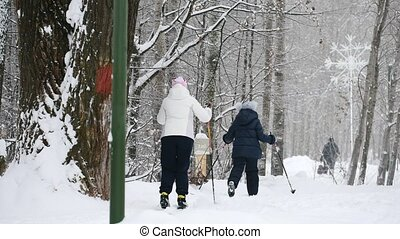 Healthy sport family - mammy and child - skiers in winter snow park