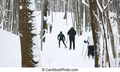 Healthy sport family moving slides ski in winter snow forest