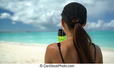 Healthy sporty Asian runner woman running on beach drinking water bottle