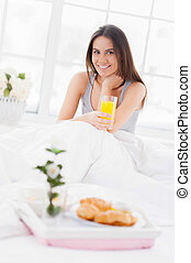Healthy start of the day. Cheerful young smiling woman holding a glass with juice while sitting in bed with a breakfast laying on tray