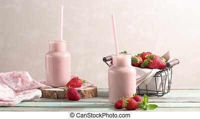 Healthy strawberry smoothie in a mason glass jar with...