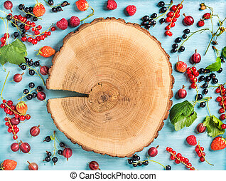 Healthy summer garden berry variety. Black and red currant, gooseberry, rasberry, strawberry, mint leaves on blue painted backdrop with round wooden board in center, copy space