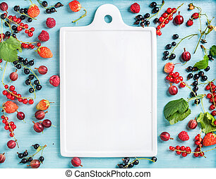 Healthy summer garden berry variety. Black and red currant, gooseberry, rasberry, strawberry, mint leaves on blue painted backdrop with white ceramic board in center, copy space
