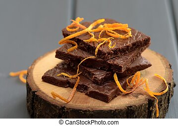 Healthy tasty dark chocolate bars with fresh orange rind on wood stands