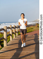 healthy teen girl jogging by the beach