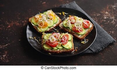 Healthy toasts with cucomber, tomatoes and crumbled feta and...