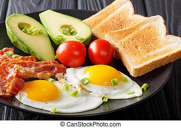 healthy traditional breakfast of fried eggs with bacon, fresh avocado, toast and tomato closeup. horizontal