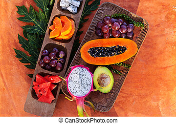 Healthy tropical fruits on wooden plate.