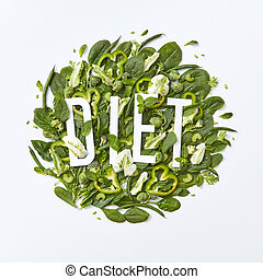 Healthy variety of green vegetables cabbage, spinach, asparagus pieces of cucumber and pepper on a gray background with a paper inscription Diet on a gray background with copy space. Flat lay