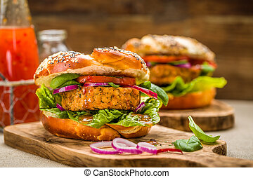 Healthy vegan burger with fresh vegetables and chili sauce