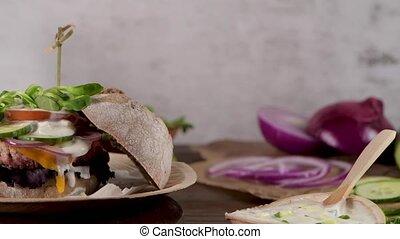 Healthy vegan burger with fresh vegetables and yogurt sauce...