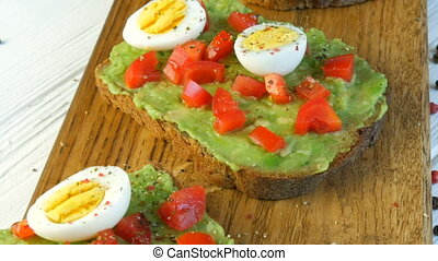 Healthy Vegan food. Spread mashed avocado on toasted brown bread sprinkled with black and red pepper. Making tasty avocado toast for breakfast. Cooking bruschetta with cherry tomatoes and quail eggs.
