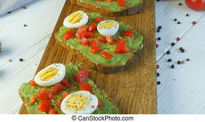 Healthy Vegan food. Spread mashed avocado on toasted brown bread with black and red pepper. Making tasty avocado toast for breakfast. Cooking bruschetta with cherry tomatoes and quail eggs.