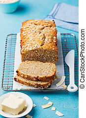 Healthy vegan oat and coconut loaf bread, cake on a cooling rack Blue stone background