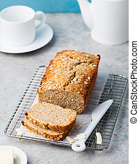 Healthy vegan oat and coconut loaf bread, cake on a cooling rack Grey stone background Copy space