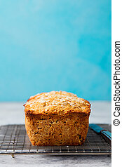 Healthy vegan oat, coconut loaf bread, cake on a cooling rack. Grey and blue background. Copy space