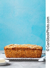 Healthy vegan oat, coconut loaf bread, cake on a cooling rack Grey and blue stone background