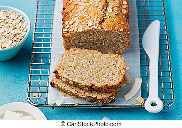 Healthy vegan oat, coconut loaf bread, cake on a cooling rack Grey and blue stone background.