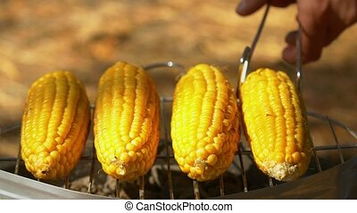 Healthy vegetarian barbecue with ripe golden corn and turn it around by using barbeque tongs