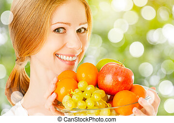 healthy vegetarian food. happy woman with a plate of fruit in summer